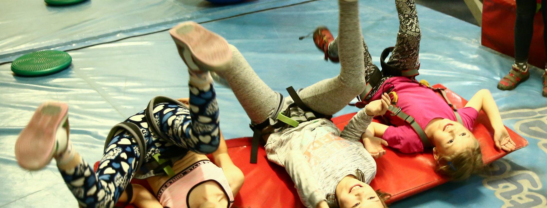 Trzy dziewczynki leżą na macie gimnastycznej i próbują zrobić fikołki