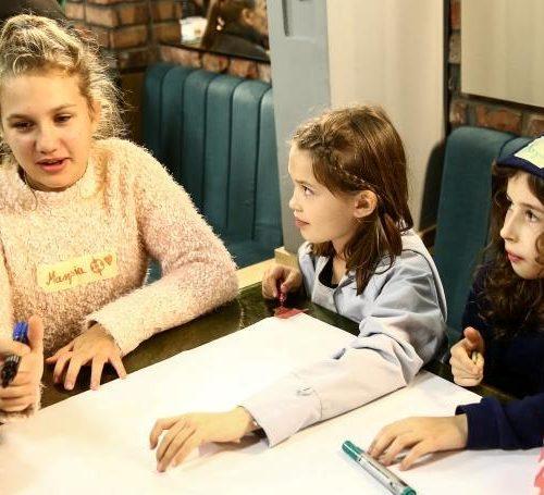 Na zdjęciu pięć dziewczynek i osoba prowadząca siedzą wokół stołu, na którym porozkładane są materiały warsztatowe - kartki, mazaki.