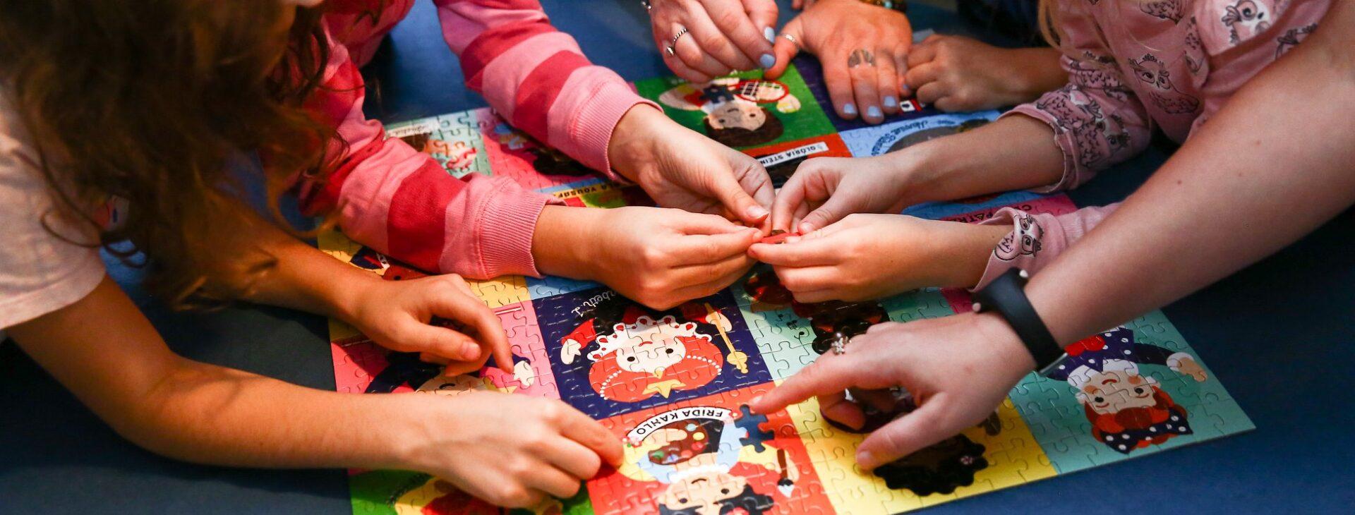 Na zdjęciu dłonie dziewczynek układających puzzle z wizerunkami ilustrowanych dziewczyn.