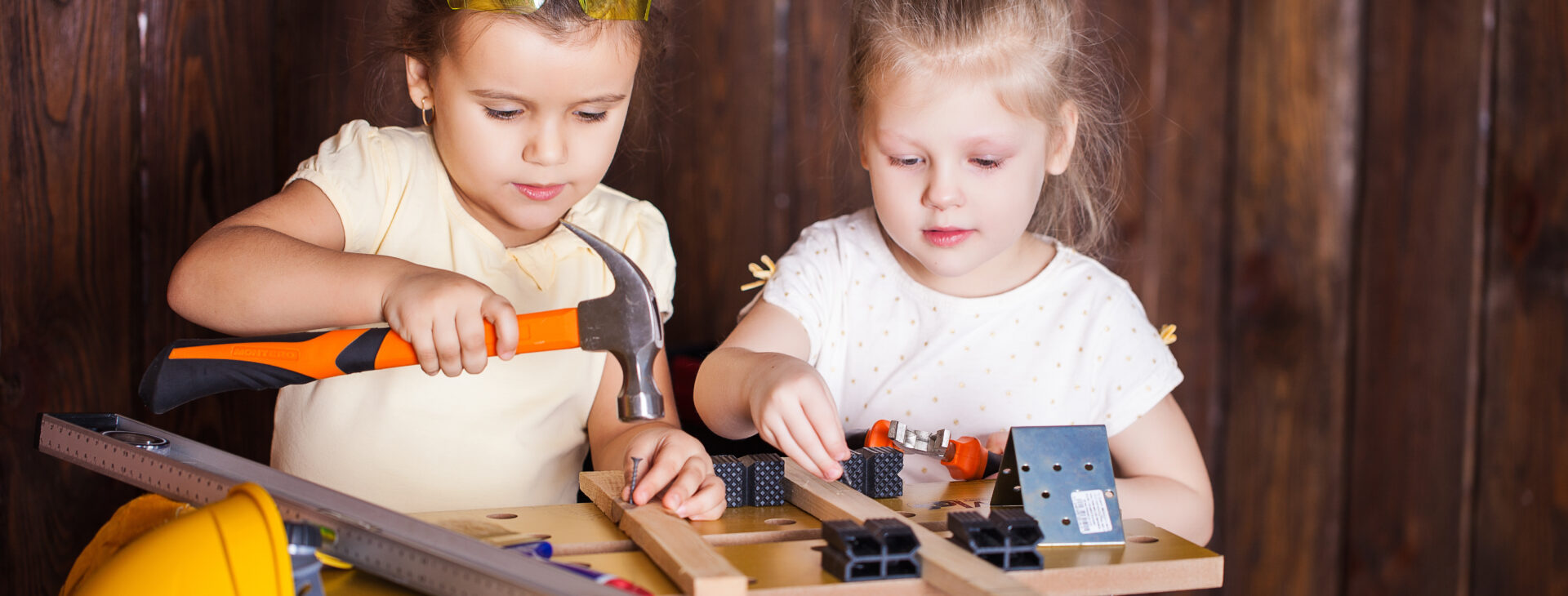 Dwie dziewczynki z młotkami w dłoniach stoją przy stole i tworzą konstrukcje w drewnie.