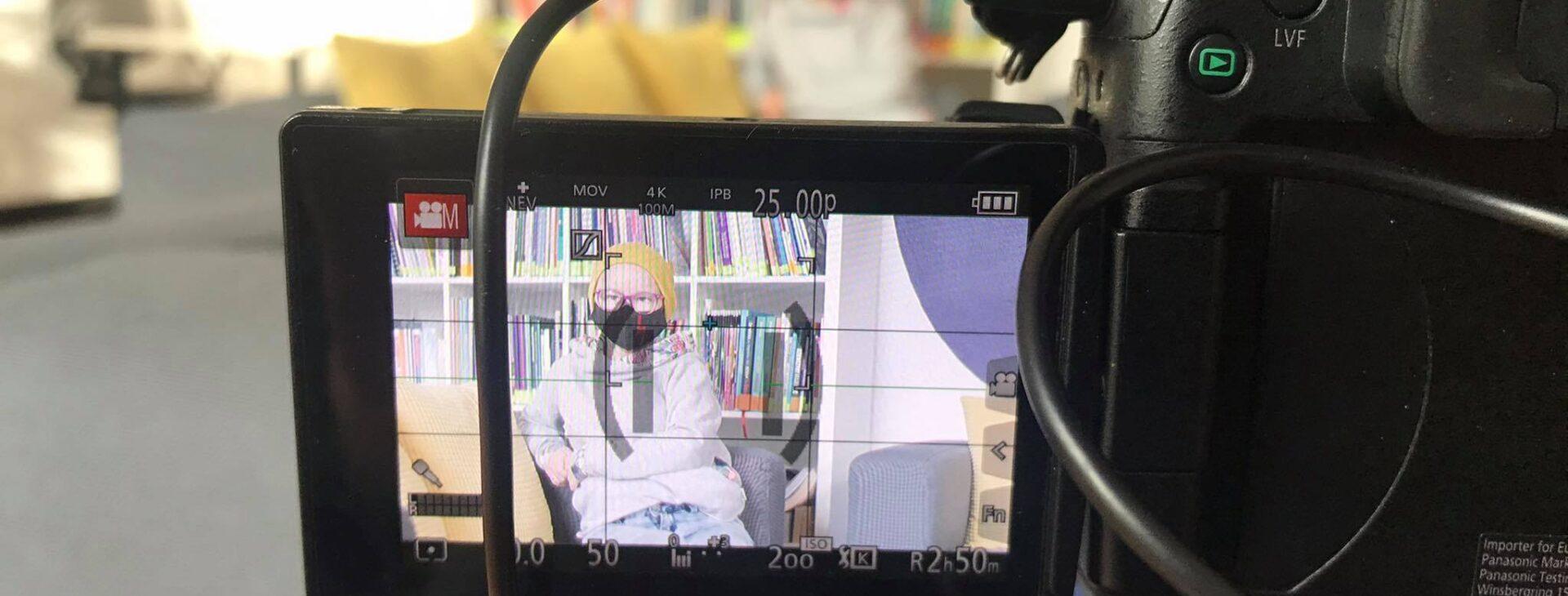 Zdjęcie przedstawia niewielki ekran przy kamerze, przed którą siedzi Katarzyna Żeglicka. W tle regał z książkami.