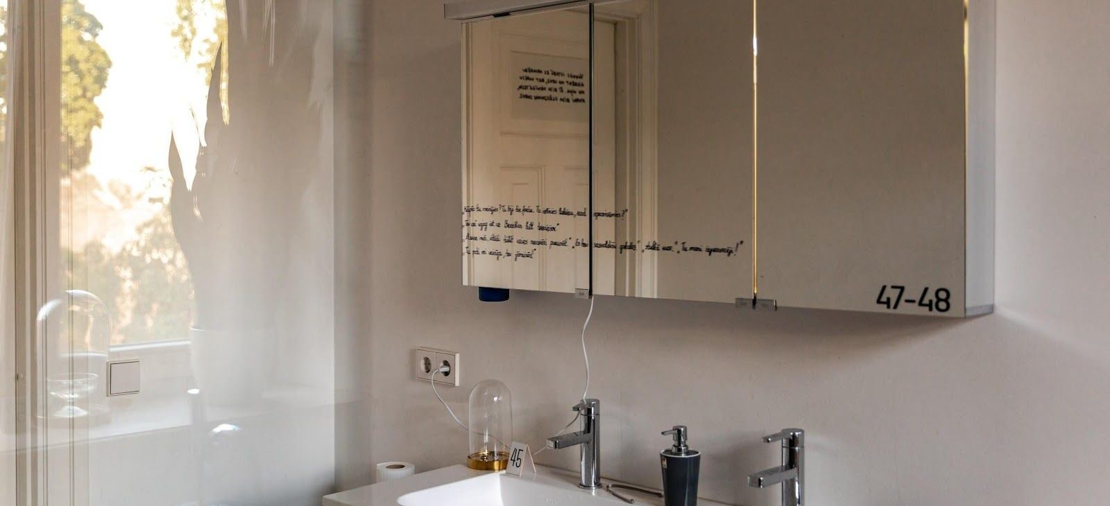 Zdjęcie z litewskiej wystawy Muzeum Dowodów Rzeczowych. Przedstawia łazienkę z lustrem, na którym markerem napisane jest świadectwo osoby. Na lustrze numer 47-48. Na umywalce pod lustrem numer 45, przy prostownicy do włosów numer 46.