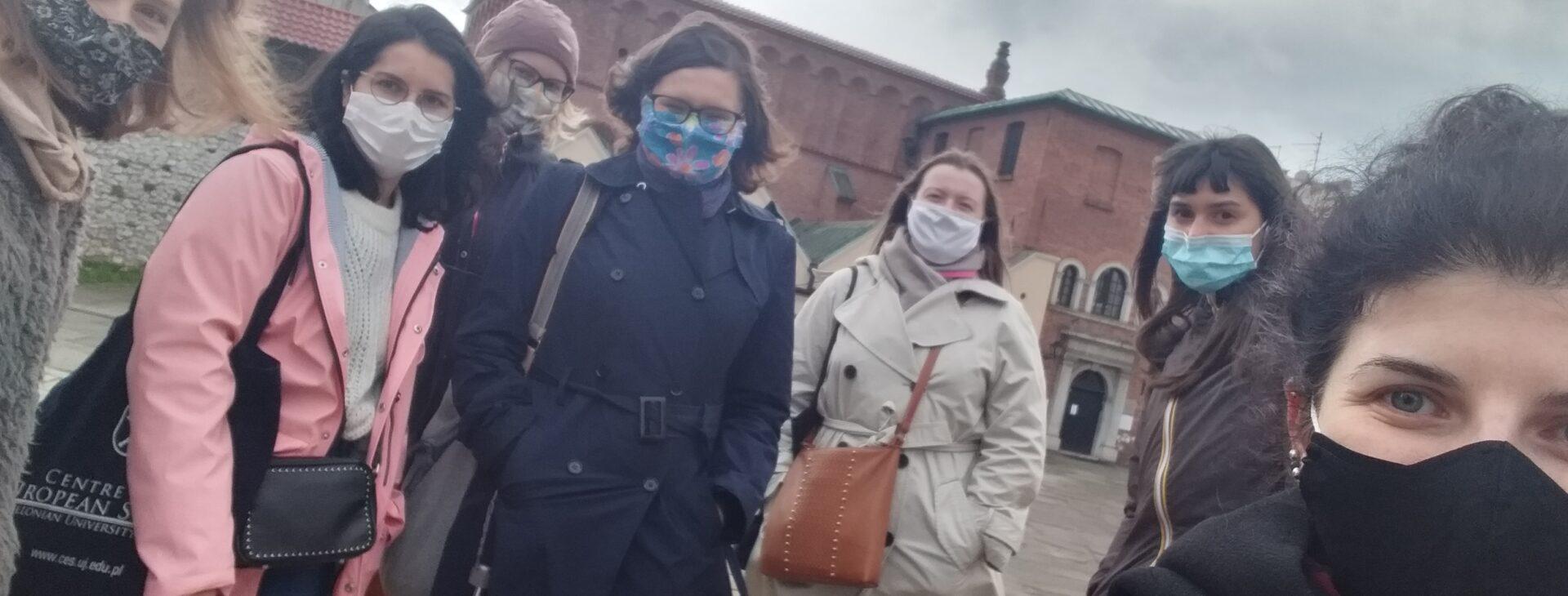7 kobiet stoi przodem do zdjęcia, ubrane są w płaszcze i kurtki, mają maski na twarzach.